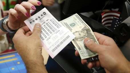 A cashier right, sells a Powerball lottery ticket