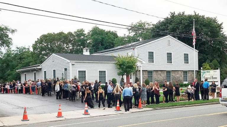Mourners gather outside McManus-Lowery Funeral Home in Medford