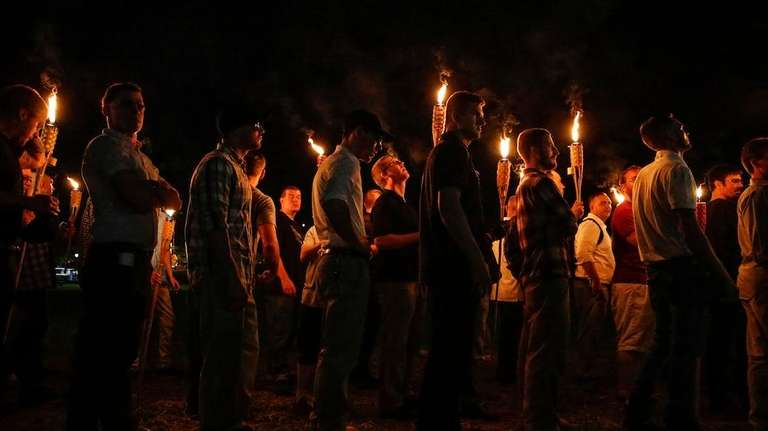 White nationalist groups march with torches through the