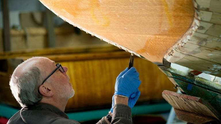 Ron Ahlers works on the transom of a