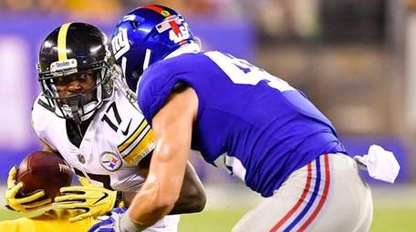 Eli Rogersof the Steelers is tackled by Calvin