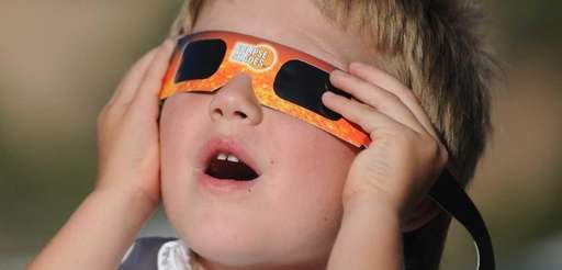 A child watches an eclipse through a safety