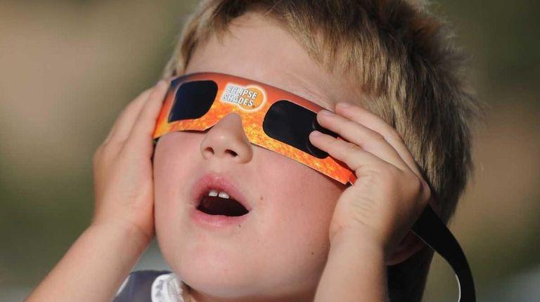 A child watches an eclipse through a safety