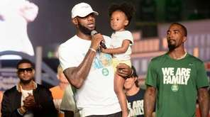 Cleveland Cavaliers' LeBron James speaks while holding his