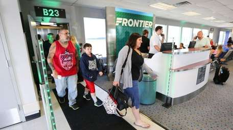 Passengers disembark a Frontier Airlines plane after the