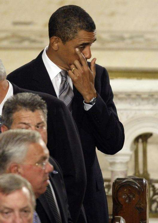 President Barack Obama wipes his eye at the