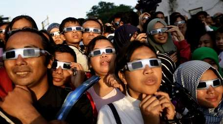 Protective gear on, people in Jakarta, Indonesia, look
