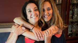 Sisters Michelle Robey, left, and Patricia DeMint hug