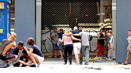 Injured pedestrians are comforted in Barcelona on Aug.