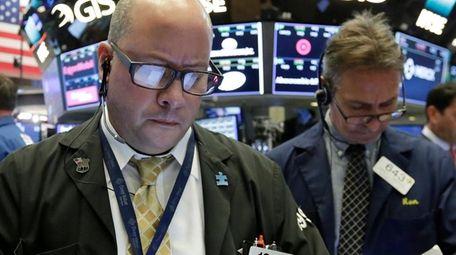 Trader Jeffrey Vazquez, left, on the floor of