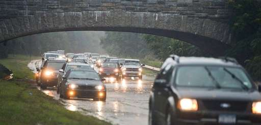 Cars navigate a flooded Southern State Parkway near