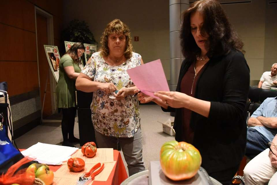 Christina Kraemer of Bohemia has her tomato weighed