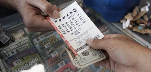 Joe Corbett of Medford buys a Powerball ticket