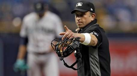 Home plate umpire Chris Guccione points to Tampa
