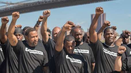 Members of law enforcement raise their fists during