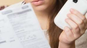 Woman looking at a phone bill.