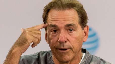 Alabama football coach Nick Saban talks with the