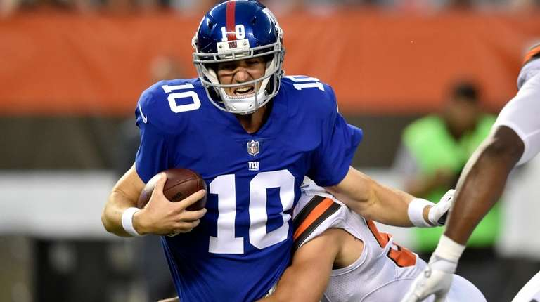 Giants quarterback Eli Manning is sacked by Browns