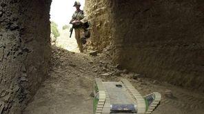 A U.S. soldier maneuvers a robot into a