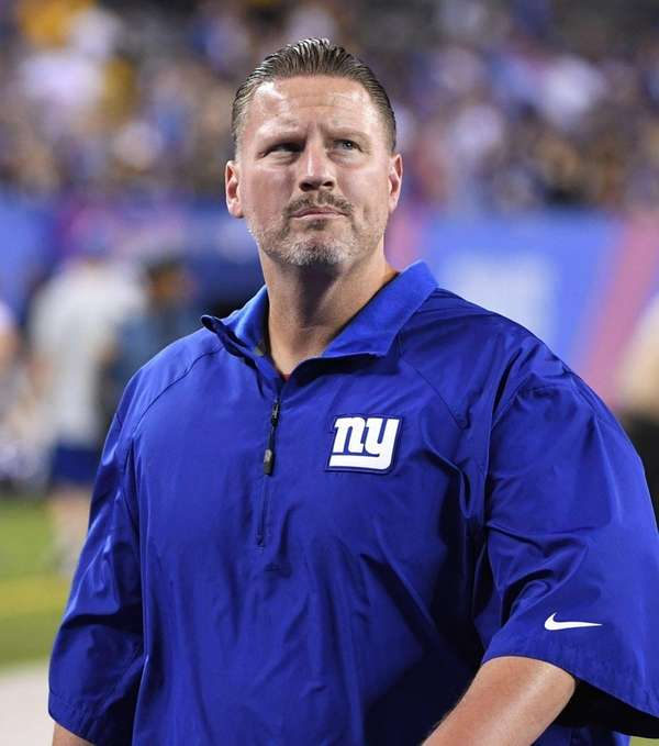 Giants head coach Ben McAdoo walks off the