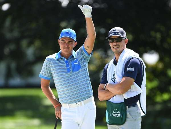 Golfer Rickie Fowler gestures on the 9th green