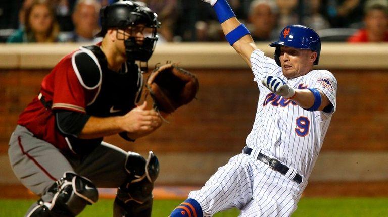 Brandon Nimmo of the Mets slides home against