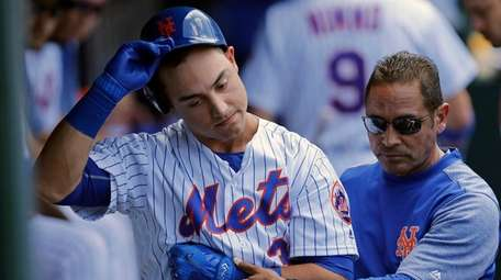 Mets outfielder Michael Conforto is helped into the