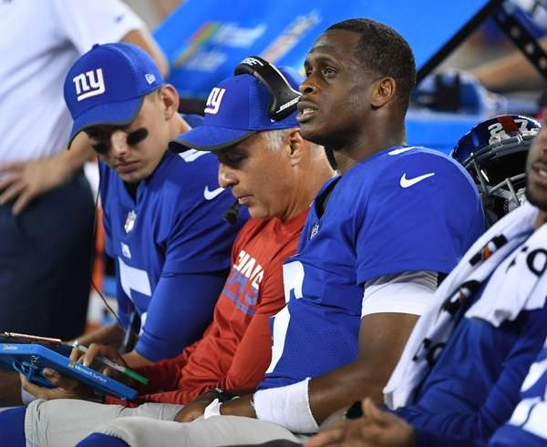 Giants quarterback Geno Smith, right, looks on from