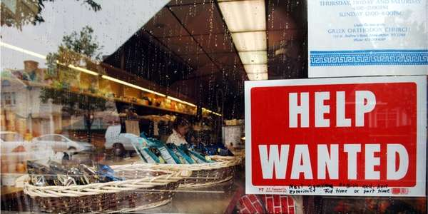 A Help Wanted sign in the window of
