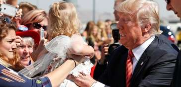 President Donald Trump tries to hold a baby