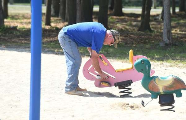 A Town of Islip worker spray-paints a children's