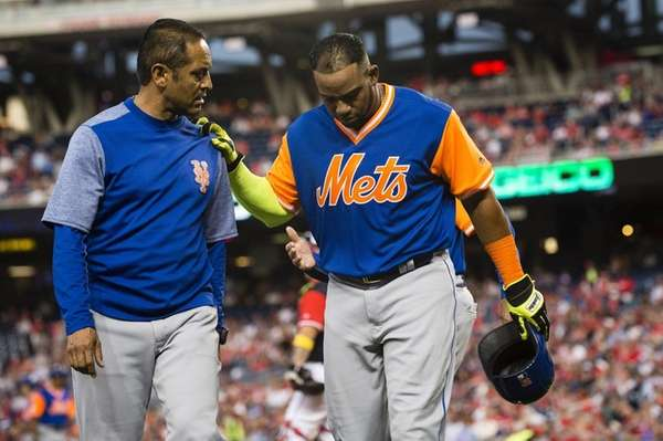 Yoenis Cespedes of the Mets is helped off