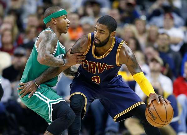 Cleveland Cavaliers' Kyrie Irving, right, looks to drive