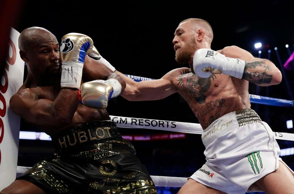 Conor McGregor, right, hits Floyd Mayweather Jr. in