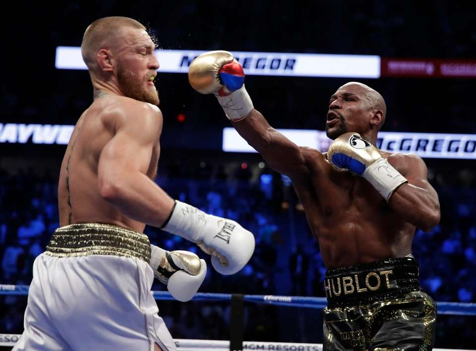 Floyd Mayweather Jr. hits Conor McGregor in a