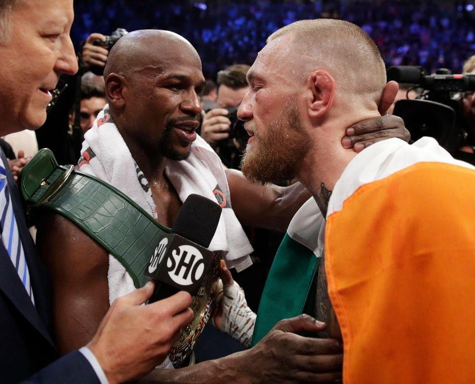 Floyd Mayweather Jr., left, embraces Conor McGregor after