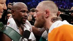 Floyd Mayweather Jr., left, embraces Conor McGregor after