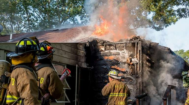 Mastic firefighters battle a house fire on Pinelawn