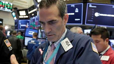 Trader Gregory Rowe works at the NYSE, Aug.