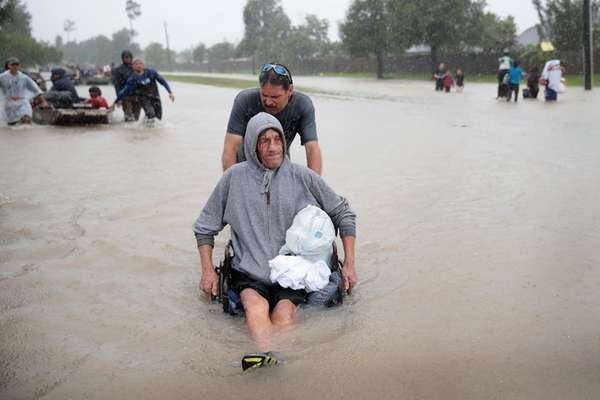 People make their way out of a flooded
