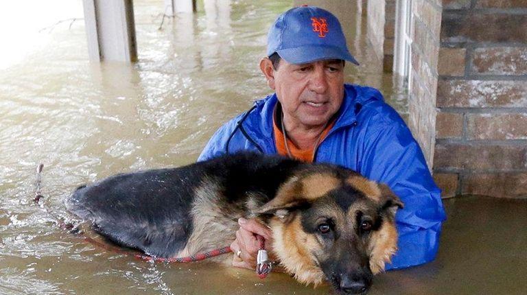 Joe Garcia carries his dog, Heidi, from his