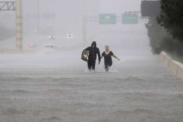 Two people walk down a flooded section of