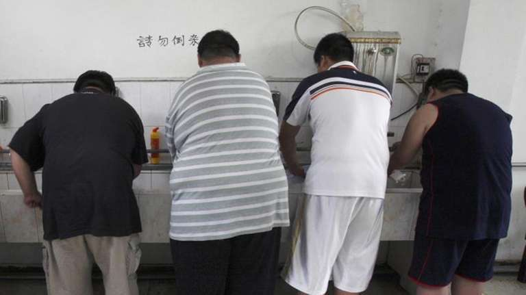 Obese patients wash their plates after lunch at