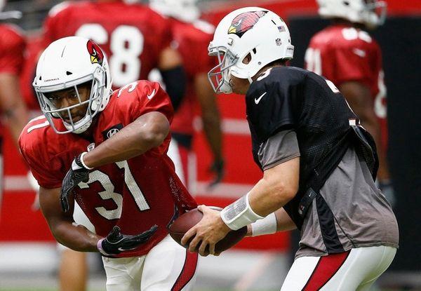 Arizona Cardinals quarterback Carson Palmer, right, fakes a