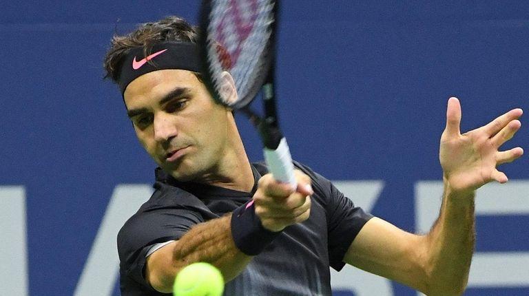 Roger Federer returns a shot to Frances Tiafoe