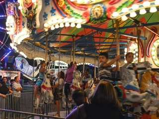 Parents look on while children ride the big