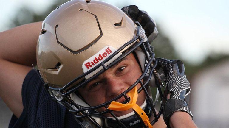 Mark Rossini fixes his helmet during practice at
