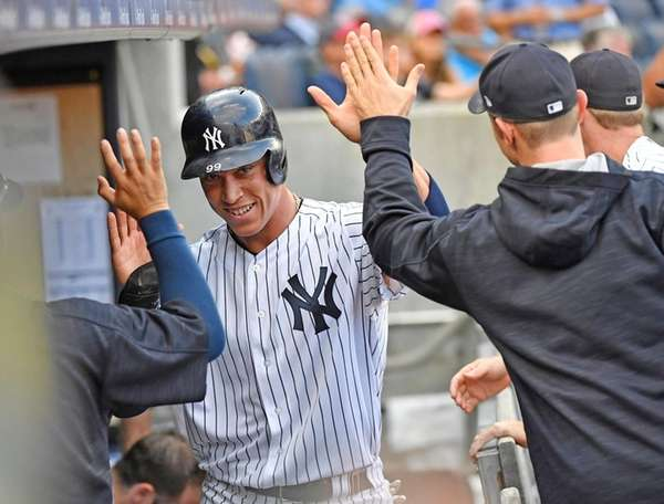 Aaron Judge is greeted in the Yankees dugout