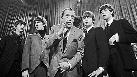 Show host Ed Sullivan gives an aside to