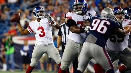 Giants quarterback Geno Smith passes under pressure from